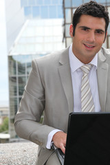 Businessman using a laptop computer outside