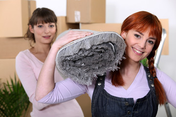 Women moving a roll of carpet