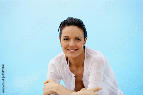 Brunette leaning at edge of pool