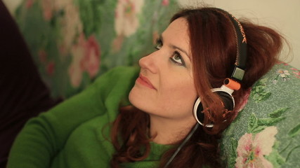 Redheaded woman uses an mp3 player
