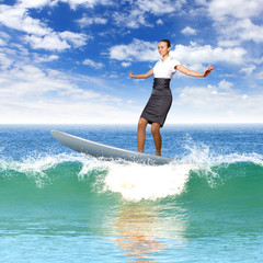 Businesswoman surfing on the sea waves