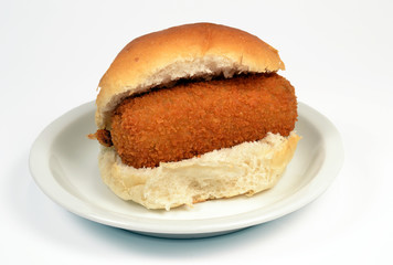 Roll with crispy calf croquette on a white context roll.