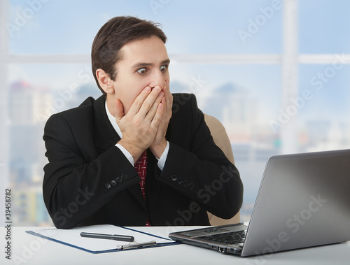 surprised  frightened businessman   looking at a laptop, his han