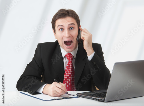 surprised  business man talking on the phone, experiences fear a
