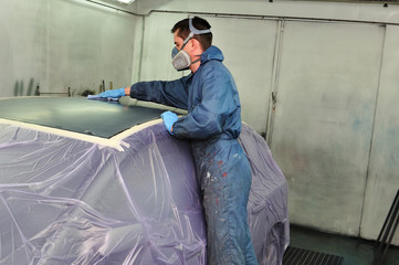 Worker preparing car roof for painting in a paint booth.