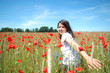 A young girl in a field of summer red poppies