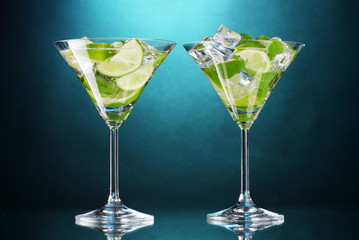 glasses of cocktails with lime and mint on blue background