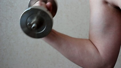 Bodybuilder deals with a dumbbell exercise.