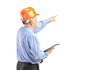Mature engineer with helmet holding a clipboard and p