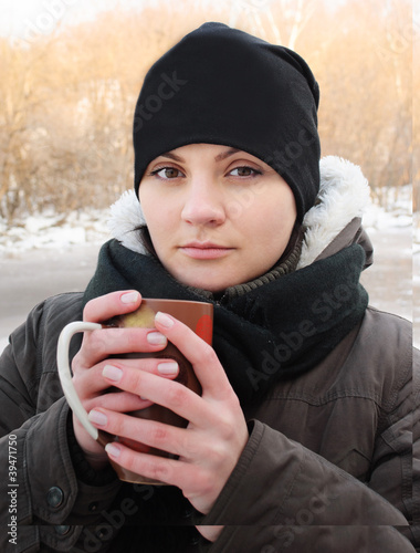 girl with a cup in his hands in the cold winter looking forward.