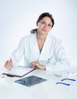 portrait of confident female doctor sitting on her desk