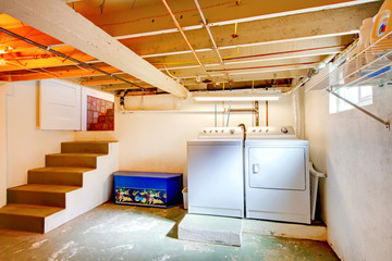 Basement laundry room with old appliances.
