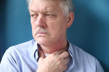 senior man with throat or neck irritation