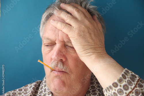 senior man with a fever and aching head