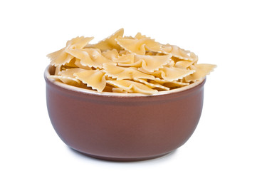 Bowl with raw pasta on a white background.