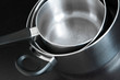 Metal saucepans on dark background