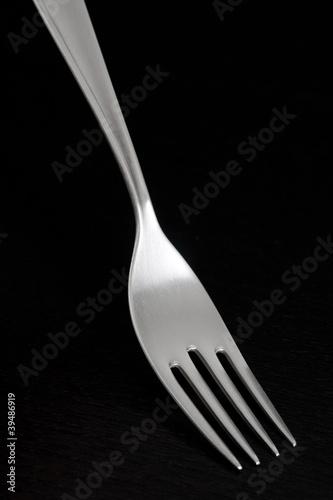 Silver fork on dark background