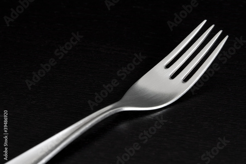 Silver fork on black background