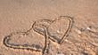 2 verschlungene Herzen am Strand