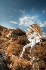Cyber woman witu umbrella in a mountains.