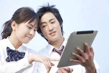 タブレットPCを触る高校生カップル