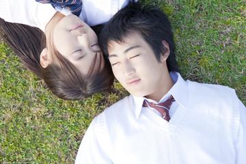 芝生に寝転ぶ高校生カップル