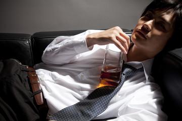 ウィスキーを持って寝転ぶビジネスマン