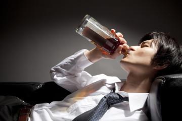ウィスキーをラッパ飲みするビジネスマン