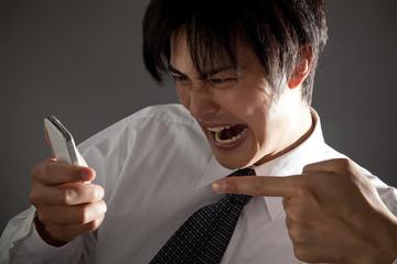 スマートフォンに向かって怒るビジネスマン