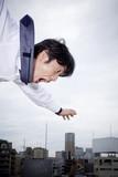 屋上から飛び降りるビジネスマン
