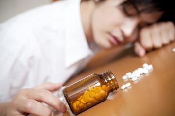睡眠薬を飲んで倒れるビジネスマン