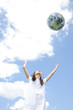 地球儀を空に向かって投げる女性