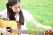 草原でギターの調弦をする女性