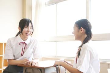 教室で会話している2人の女子中学生