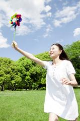 風車を持って芝生を駆ける女性