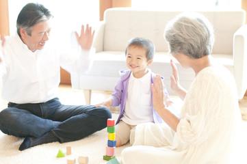 孫と積み木で遊ぶ祖父母