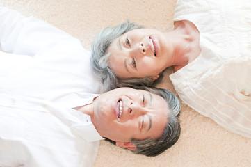 寝転んで微笑むシニアカップル