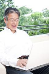 ノートパソコンを見る笑顔のシニア男性