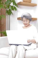 ノートパソコンを見るシニア女性