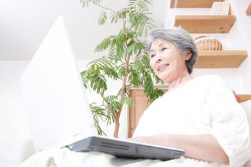 ノートパソコンを見る笑顔のシニア女性