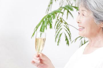 シャンパングラスを持って微笑むシニア女性