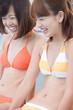 プール際ではしゃぐ水着女性2人
