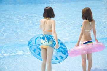 浮き輪を持った水着女性2人の後姿