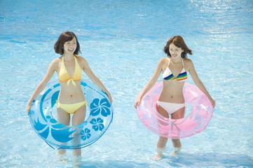 プールで遊ぶ水着女性2人