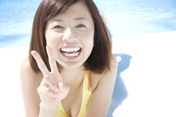 プール際に寝そべってピースをする水着女性