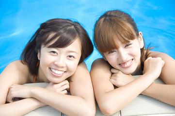 プール際で微笑む水着女性2人