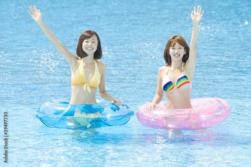 プールで手を振る水着女性2人