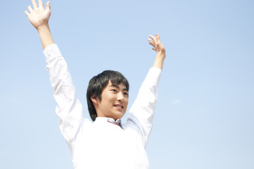 両手を挙げて微笑む男子高校生