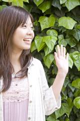 笑いながら友達に手を振る女性