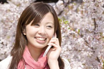 桜の下で電話をする女性